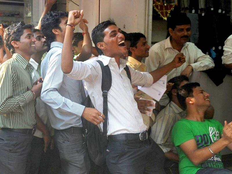 Fans celebrate as they watch cricketer Sachin Tendulkar scoring his 100th century, on a television set inside a shop in Mumbai. Sachin Tendulkar became the first batsman in history to score 100 international centuries, adding another milestone in his record-breaking career. AFP Photo
