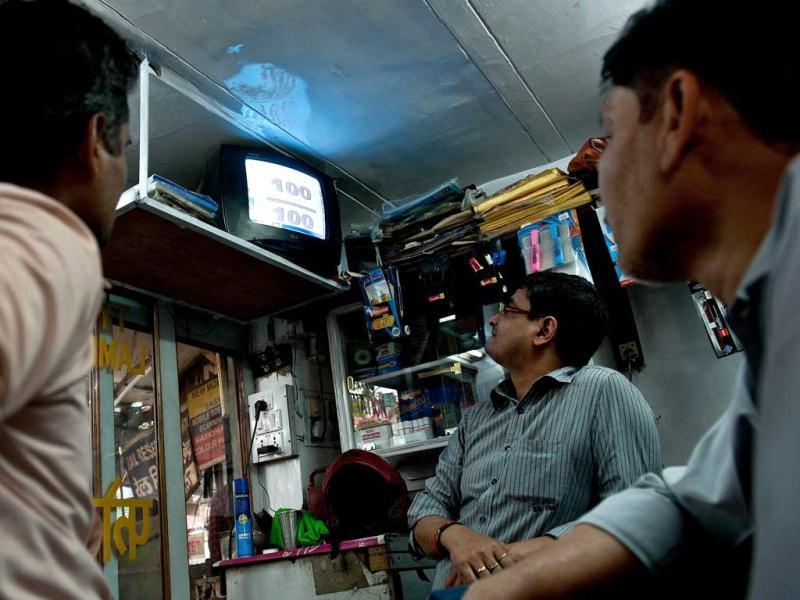 Fans watch batsman Sachin Tendulkar batting during the Asia Cup cricket match between India and Bangladesh on a television at a shop in New Delhi. Sachin Tendulkar on March 16 became the first batsman in history to score 100 international centuries, adding another milestone in his record-breaking career. AFP Photo