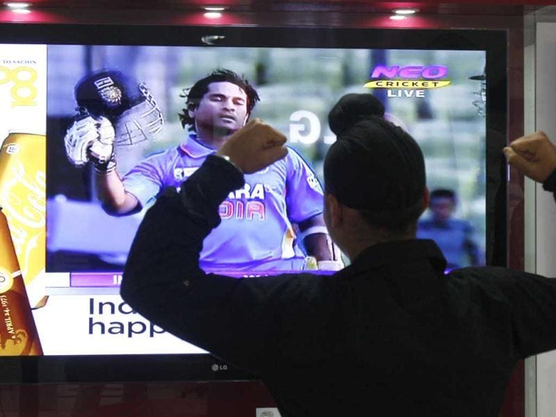 A young cricket fan celebrating completion 100 hundreds by Sachin Tendulkar during one day match against Bangladesh, at an electronic showroom in Amritsar on Friday.HT Photo/Munish Byala