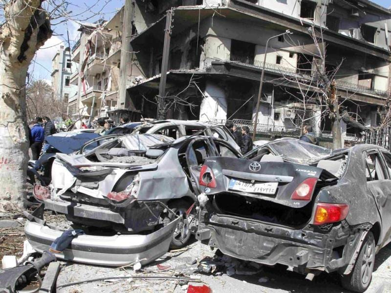 Damaged vehicles are seen at the site after two explosions near the intelligence centre building in Damascus. Two large explosions hit Damascus on Saturday, killing several security force personnel and civilians, state television reported, blaming what it said were terrorists behind the year-long uprising against President Bashar al-Assad. (Reuters)