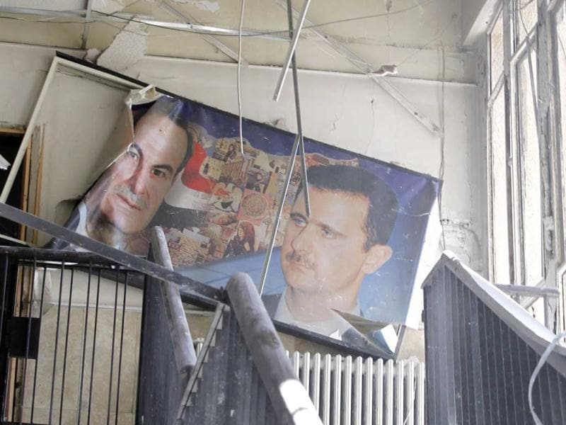A picture of Syria's President Bashar al-Assad (R) and his father, the late president Hafez, is seen at the site of an explosion in a police building in Damascus. Two large explosions hit Damascus on Saturday, killing several security force personnel and civilians, state television reported, blaming what it said were terrorists behind the year-long uprising against President Bashar al-Assad. (Reuters)