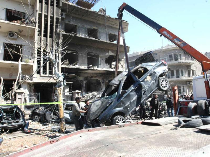 A damaged vehicle is removed outside a damaged building following twin bomb attacks on security buildings in the capital Damascus. Several civilians and police were killed, the state television reported without giving figures, adding that preliminary reports suggested bombers had blown up vehicles packed with explosives. (AFP Photo)