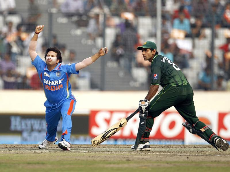 Sachin Tendulkar, left, reacts after getting hurt in an attempt to catch the ball as Pakistan's Mohammad Hafeez runs to make it to the crease during their Asia Cup cricket match in Dhaka. AP/Aijaz Rahi