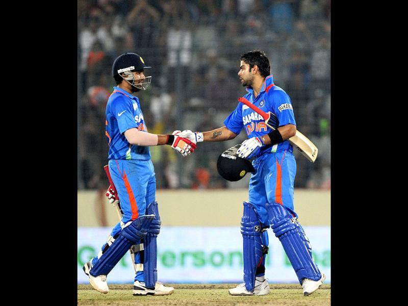 Virat Kholi (R) shakes hand with his teammate Rohit Sharma after scoring a century during the one day international Asia Cup cricket match at The Sher-e-Bangla National Cricket Stadium in Dhaka. AFP/Munir uz Zaman