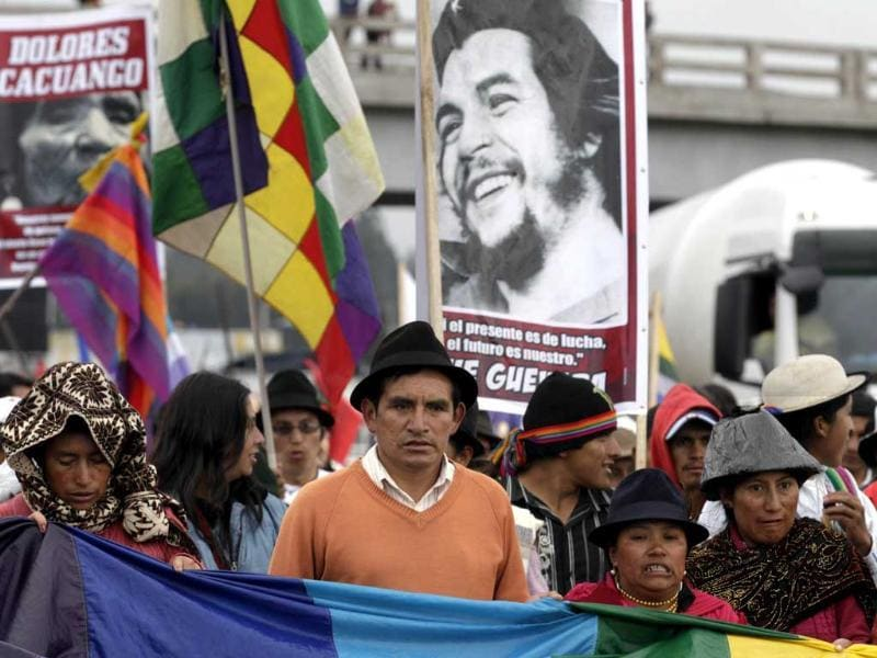 Carrying signs with images of late Indigenous leader Dolores Cacuango, left, and Argentinean born Cuban revolution leader Ernesto