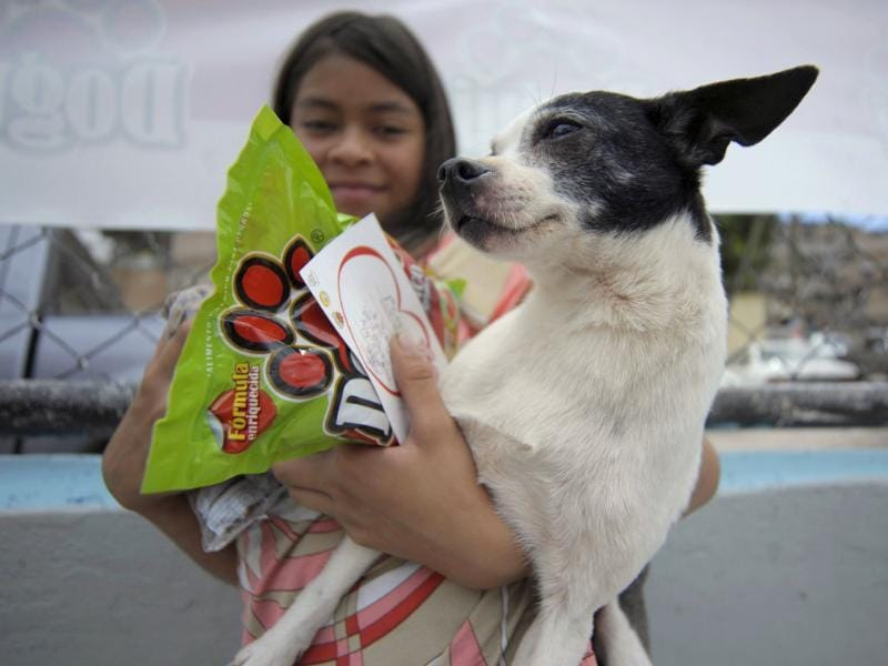 A girl shows her dog, a certificate and a bag of dog treats after its vaccination at a basketball court in Tegucigalpa. Reuters/Jorge Cabrera