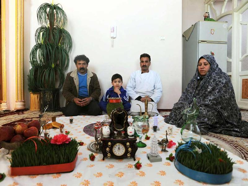 An Afghan family sits at their 'haftsin' table of traditional symbolic decorations to celebrate their new year Nowruz in Herat. AFP Photo/ Aref Karimi