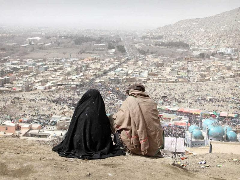 An Afghan couple sits on a hill overlooking a celebration of the Persian New Year Nowruz at the Kart-e-Sakhi shrine in Kabul. AP Photo/Musadeq Sadeq