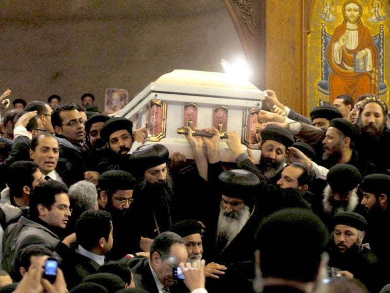 Pallbearers carry the coffin of Coptic Pope Shenuda III out of Saint Mark's cathedral during his funeral service in Cairo's al-Abbassiya district before heading to the final resting place in the 4th century Bishoy monastery in Beheira province. The late pope died on March 17 at the age of 88 after a long battle with illness leaving behind a community increasingly anxious about the rise of Islamism and political uncertainty. AFP Photo/Mohammed Hossam