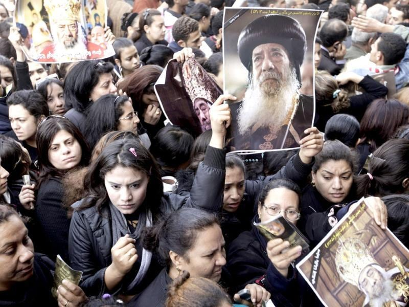 Egyptian Christians hold posters of Pope Shenouda III, the patriarch of the Coptic Orthodox Church who led Egypt's Christian minority for 40 years at a time of increasing tensions with Muslims, during his funeral at Mar Morqos, or St. Mark Coptic Orthodox Church in Cairo, Egypt. AP Photo/Amr Nabil