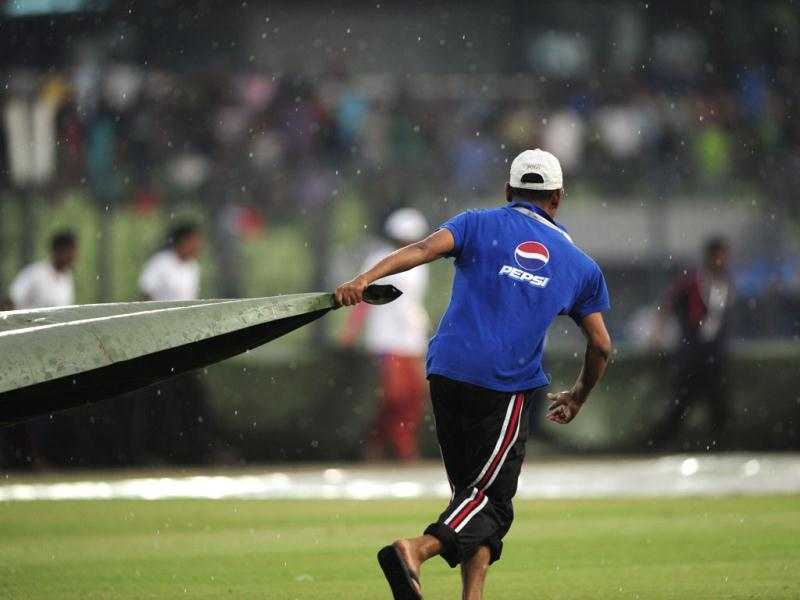 A Bangladeshi grounds boy covers the field to protect the ground from rain during the one day international (ODI) Asia Cup cricket match between Bangladesh and Sri Lanka at The Sher-e-Bangla National Cricket Stadium in Dhaka. AFP PHOTO/Munir uz ZAMAN