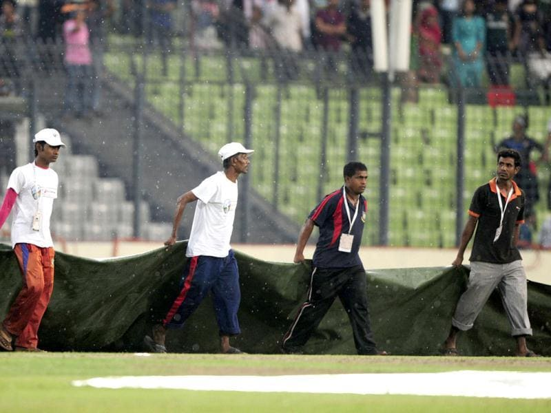 Bangladeshi grounds boys cover the field to protect the ground from rain during the one day international (ODI) Asia Cup cricket match between Bangladesh and Sri Lanka at The Sher-e-Bangla National Cricket Stadium in Dhaka. AFP PHOTO/Munir uz ZAMAN