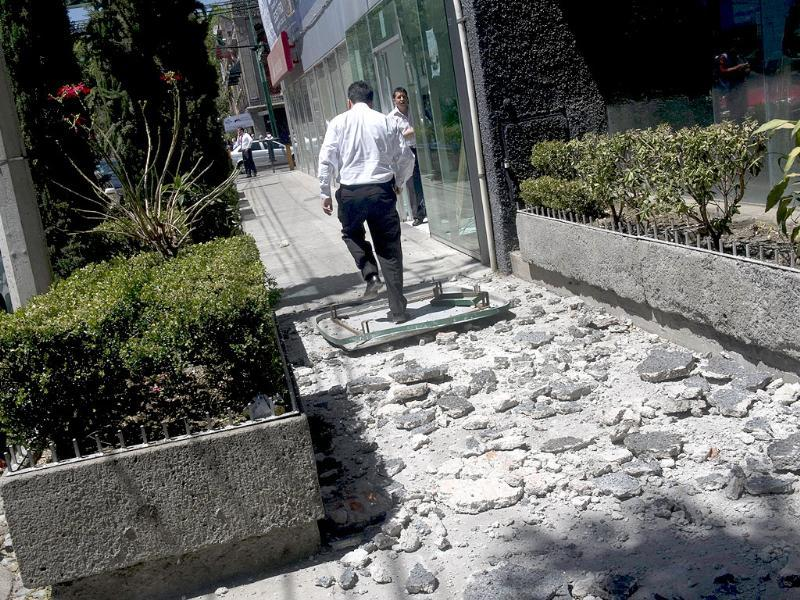 A man walks over the debris that fell from a building damaged in Mexico City during a strong quake that hit Mexico. AFP Photo/Yuri Cortez