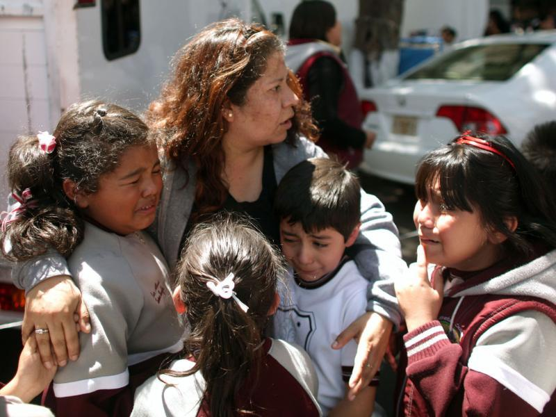 A woman comforts her crying children outside a school in the Roma neighborhood after a earthquake was felt in Mexico City. AP Photo/Alexandre Meneghini