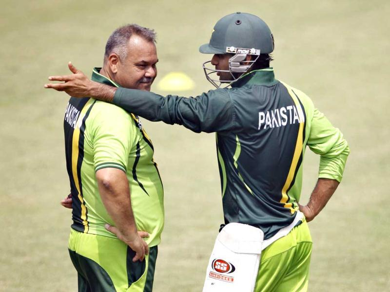 Pakistan's Mohammad Hafeez, right, talks to team coach Dav Whatmore during a training session in Dhaka, Bangladesh. AP Photo/Aijaz Rahi.