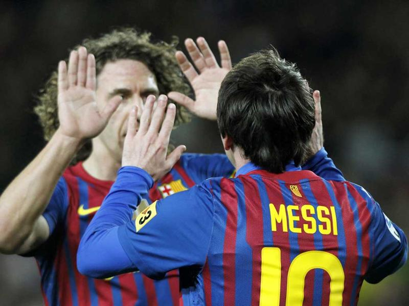 Lionel Messi celebrates a goal against Granada with teammate Carles Puyol during their Spanish First division soccer match at Camp Nou stadium in Barcelona. Messi equalled Barcelona's 60-year-old goal-scoring record of 232 with that goal. Reuters/Albert Gea