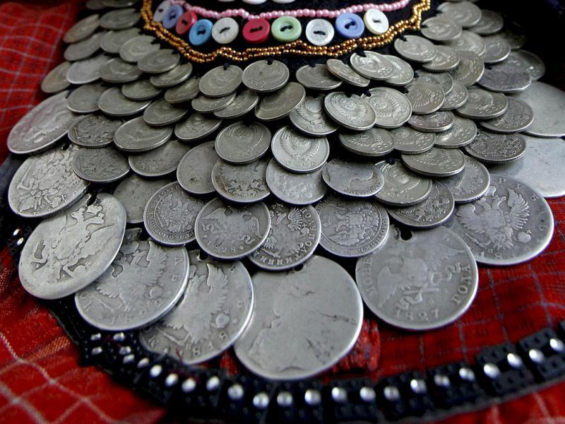 A detail of a decorative heirloom necklace made from coins worn by a member of the singing group