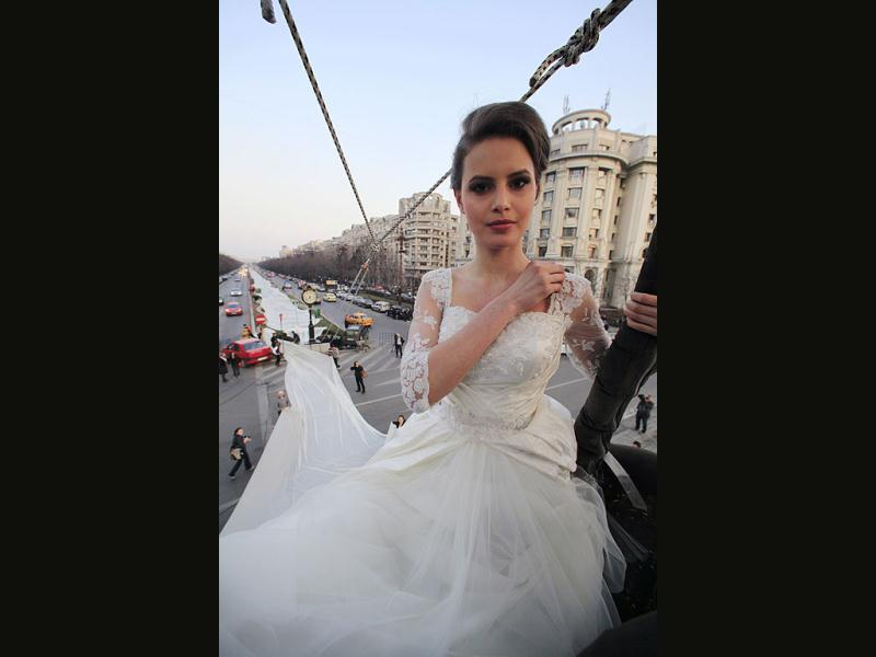 Emma, a 17 year-old model, sits on a hot air balloon as she wears the wedding dress with the longest tail in the world during a Guinness World Record attempt in Bucharest, March 20, 2012. The 2,750 meter long train broke a previous record of 2,488 meters. It is made of 4,700 meters of material using 1,857 needles, taking 100 days to made. Reuters/Radu Sigheti