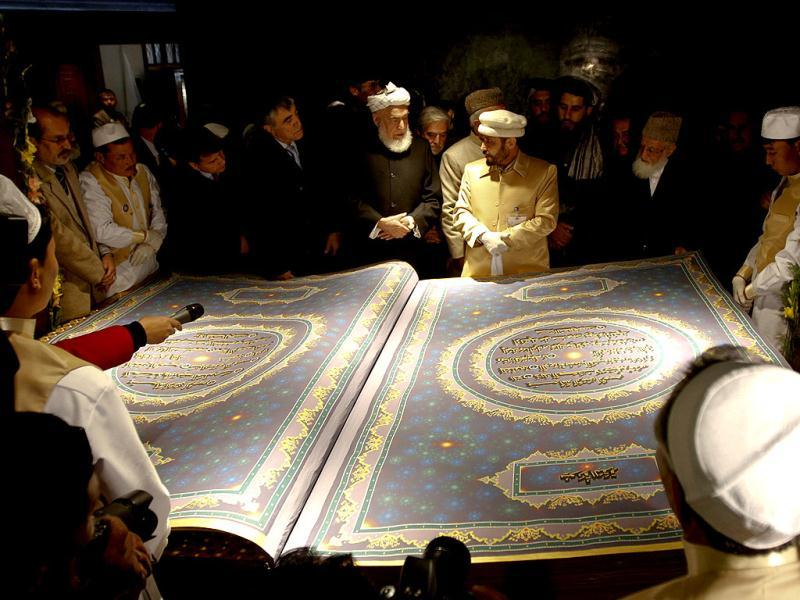Calligrapher Mohammad Sabir Khedri (centre right) gives information about the biggest Koran in the world during its inauguration ceremony in the Hakim Nasir Khosrow Balkhi library in Kabul on January 12, 2012. The Afghan calligrapher has worked for five years to create the world's biggest Koran. Reuters/Mohammad Ismail