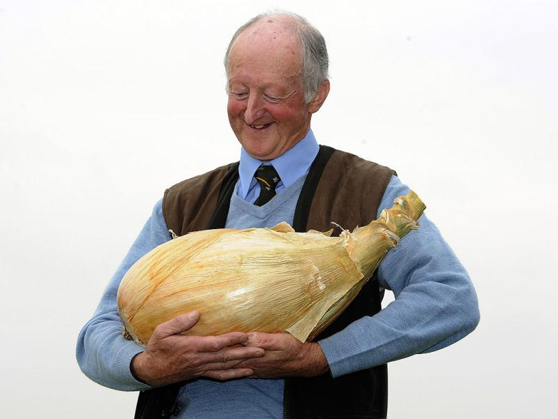 Grower Pete Glazebrook poses for photographers with his onion weighing 17lb 15.5oz (8.150kg), that now holds the world record holder for being the heaviest onion, at the Harrogate Autumn Flower Show in Harrogate, northern England on September 16, 2011. Reuters