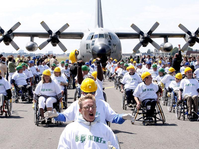People in wheelchairs react after managing to pull a C130 cargo aircraft weighing 67 tons across 100 metres at the Melsbroek military airport near Brussels on May 29, 2011. The attempt, led by 84 people, set a new Guinness World Record for heaviest plane pulled over 100 metres by a team of people in wheelchairs. Reuters/Sebastien Pirlet