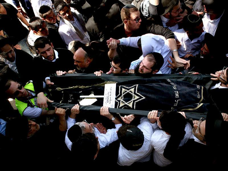 The body of seven-year-old Miriam Monsonego is carried by relatives during the funeral of victims of Toulouse school shooting, at the Givat Shaun cemetery in Jerusalem. AFP/Gali Tibbon