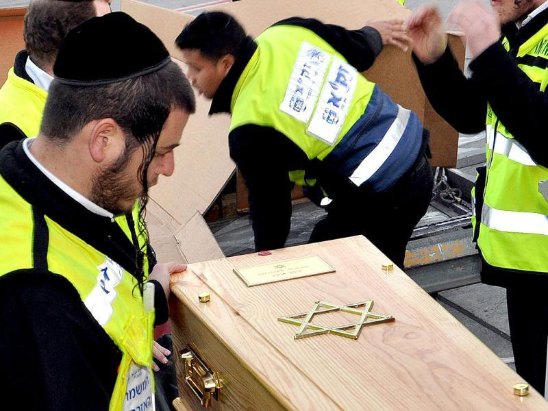 A handout photograph by the Israeli volunteers shows volunteers carrying one the coffins bearing slain victims from the Ozar Hatorah Jewish school in Toulouse. AFP/Shuki Lerer