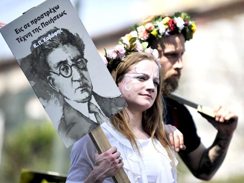 Performers hold a poster featuring Greek poet Costandinos Cavafis during a demonstration by Greek poets and artists marking the World Poetry Day. AFP Photo/Louisa Gouliamaki