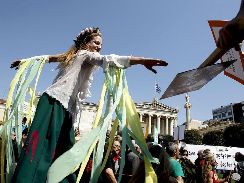 Dancers on stilts perform in front of the Athens Academy during a protest by Greek poets, in central Athens. AP Photo/Petros Giannakouris