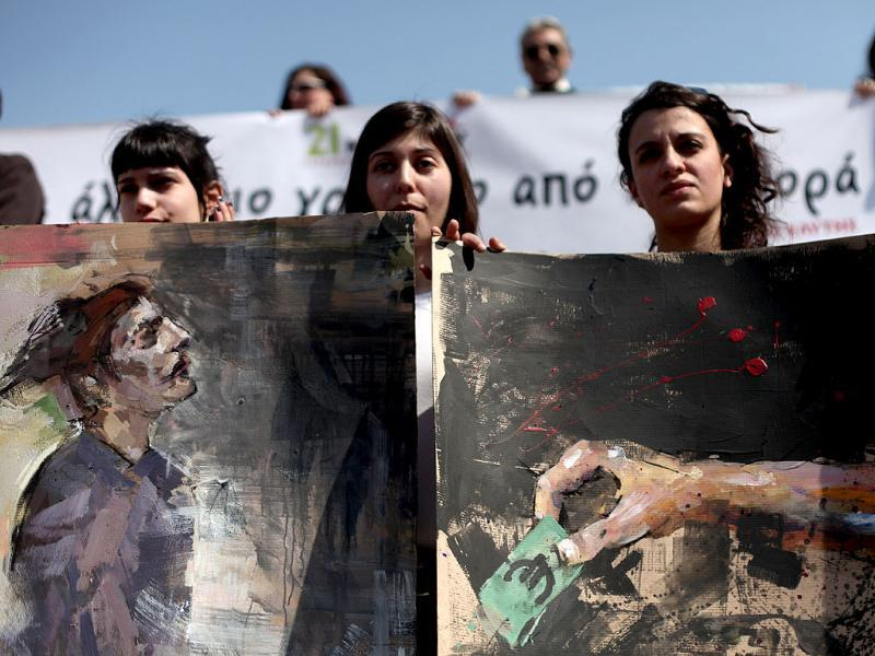 Demonstrators hold up their paintings during a protest by Greek poets, in central Athens. AP Photo/Petros Giannakouris