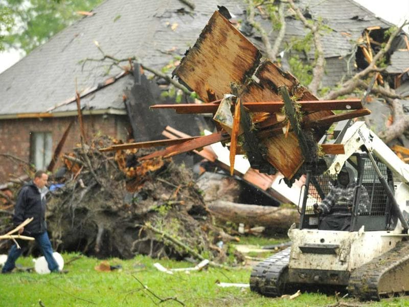 A forklift driver clears debris from destroyed homes in Prairieville, La. after a tornado struck the town. (AP Photo)
