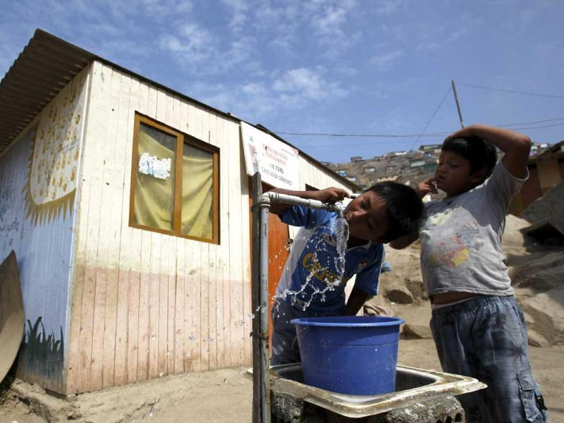 In this file photo, Pablo drinks water from an outdoor faucet as friend Nestor waits his turn outside their school in the Nueva Esperanza shantytown in Lima, Peru. On UN World Water Day, today, the organization estimates that more than one in six people worldwide do not have access to safe freshwater to ensure their basic daily needs for drinking, cooking and cleaning. (AP Photo)