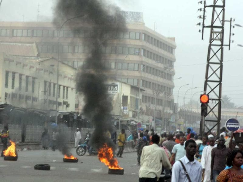 Civilians walk past burning tires lit in support of mutinying soldiers, in Bamako, Mali. Gunshots could still be heard in the Malian capital late Wednesday, hours after angry troops started a mutiny at a military base near the presidential palace. Soldiers stormed the offices of the state broadcaster, yanking both TV and radio off the air.(AP Photo)