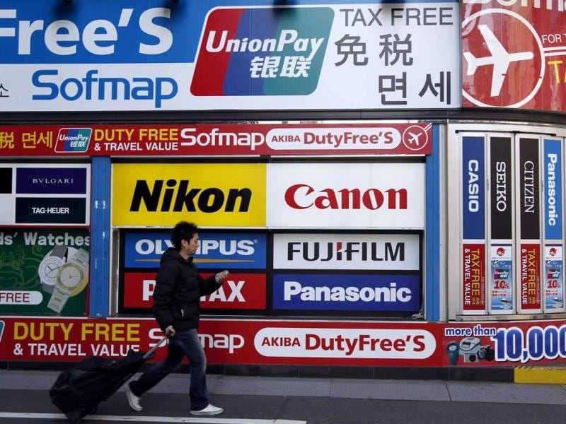 A man walks past an advertisement board featuring Chinese bank card
