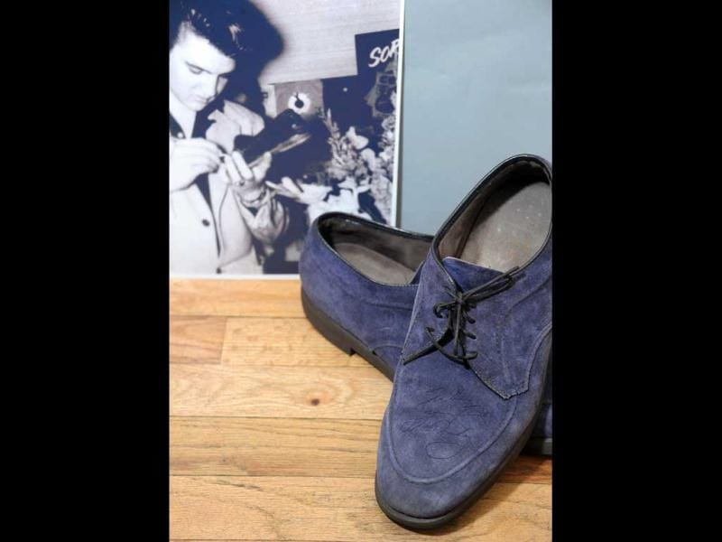 An autographed pair of Elvis Presley's original Blue Suede Shoes and a photo of him autographing them on auction at Gotta Have It! store in New York City. (Michael Loccisano/Getty Images/AFP)