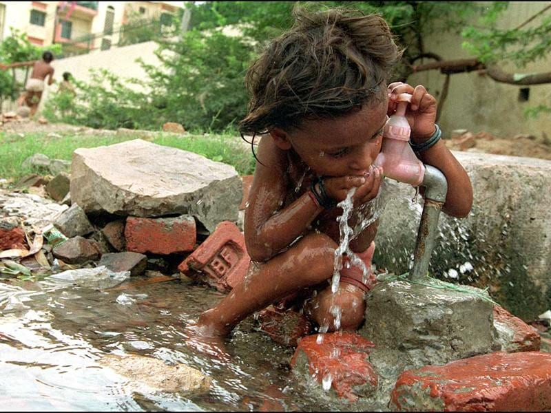 A street child drinks water straight from a tap near a gutter. HT Photo/Sunil Saxena