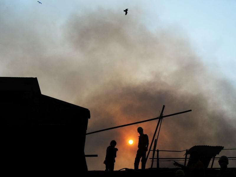 Fire-fighters work amongst the burnt remains of the Hatibagan market in Kolkata. AFP Photo/Dibyangshu Sarkar