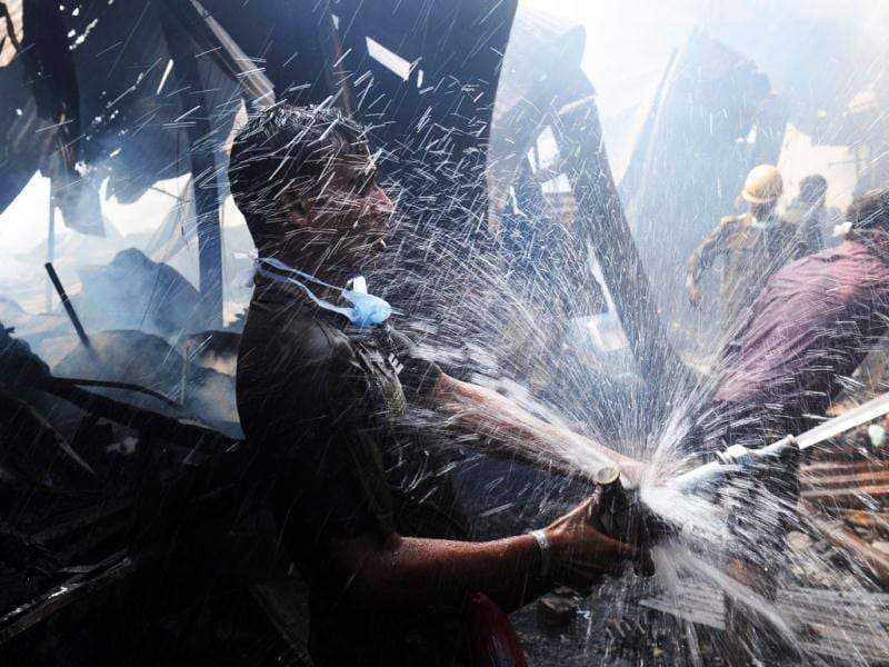 A man helps to douse a fire at the Hatibagan market in Kolkata. AFP Photo/Dibyangshu Sarkar