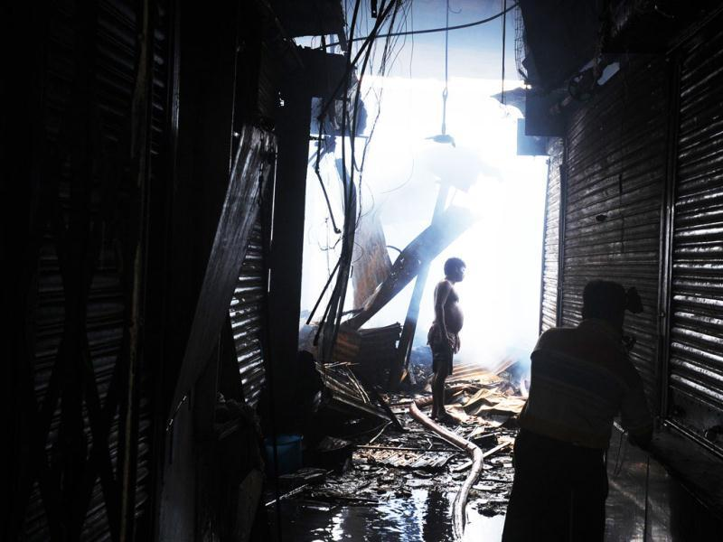 Shopkeepers look for belongings in the burnt remains of his shop at the Hatibagan market in Kolkata. AFP Photo/Dibyangshu Sarkar