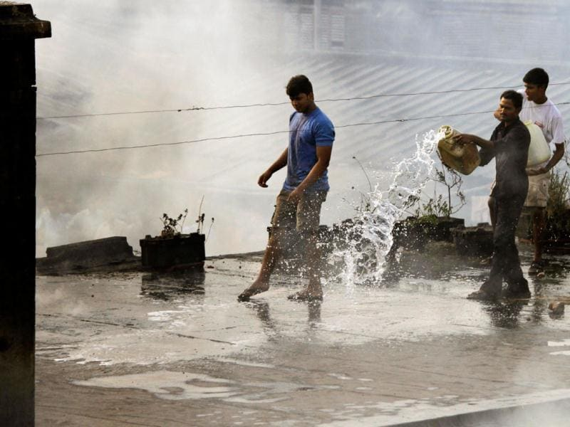 Local residents work to extinguish a fire atop a two story building at Hatibagan market in Kolkata. AP Photo/Bikas Das