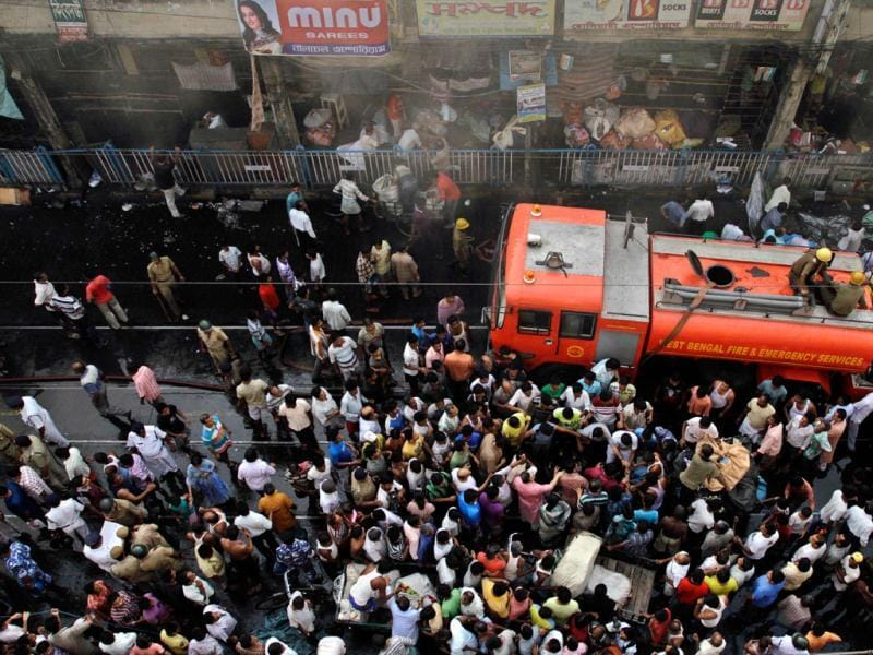 Firefighters work to extinguish a fire as civilians gather at Hatibagan market in Kolkata. AP Photo/Bikas Das