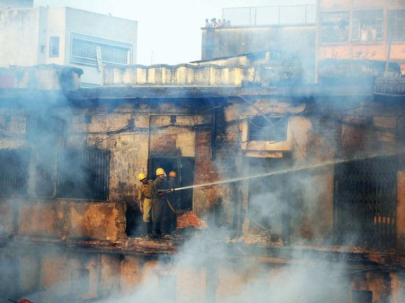 Fire-fighters work to douse a fire at the Hatibagan market in Kolkata. AFP Photo/Dibyangshu Sarkar