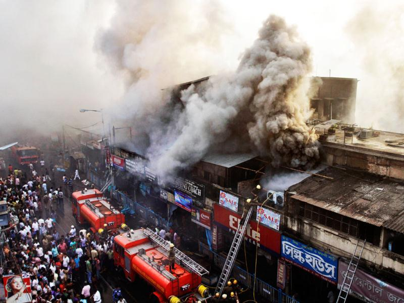 Firefighters work to extinguish a fire as smoke billows from Hathibagan market building in Kolkata. A large number of shops at the Hatibagan market in north Kolkata were reduced to ash in a devastating blaze that broke out in the early hours. AP Photo/Bikas Das