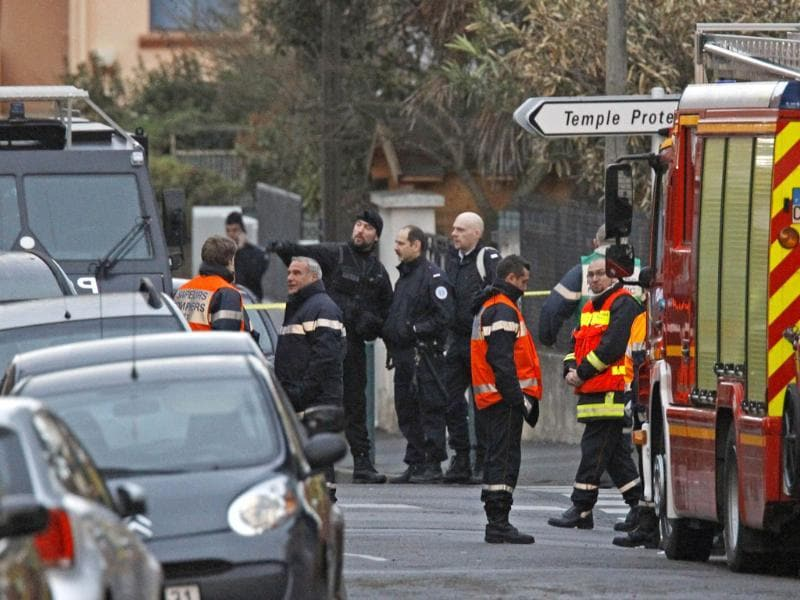 Police officers and firefighter stand next to an apartment building in Toulouse, where Mohamed Merah, a suspect in the shooting at he Ozar Hatorah Jewish school, had been holed up. AP Photo/Remy de la Mauviniere