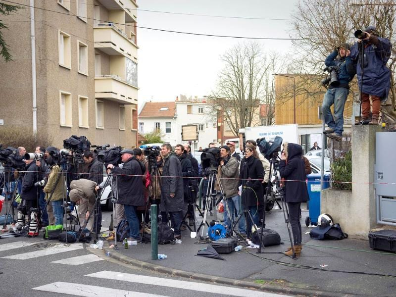 Journalists wait as French policemen and firefighters and members of the RAID special police forces unit are still laying siege to the apartment block where Mohamed Merah, the man suspected of a series of deadly shootings, was holed up in Toulouse, southwestern France. AFP Photo/Lionel Bonaventure