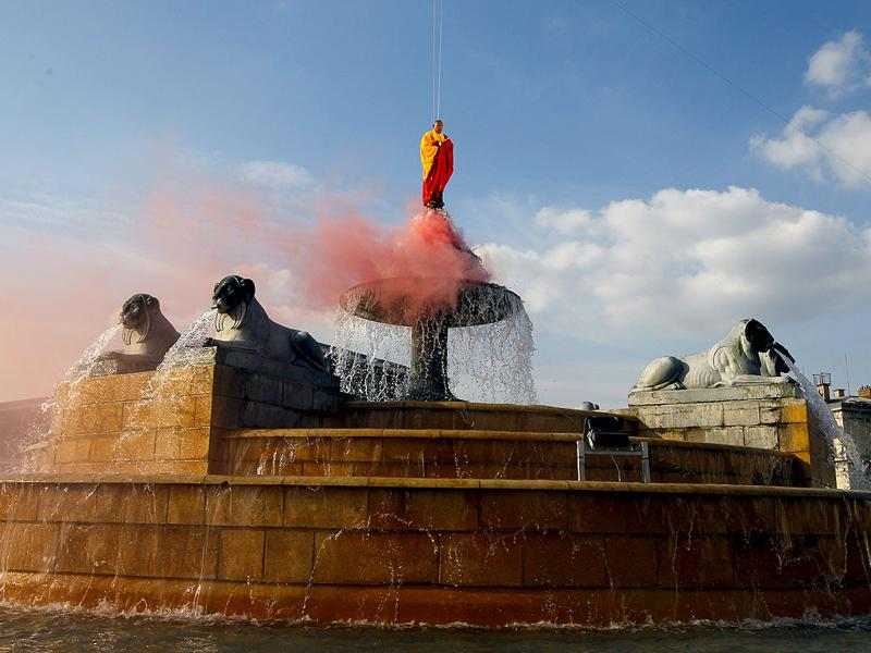 Suspended by wires, Chinese artist Li Wei performs in the sky over the Fontaine of Lyons at La Villette in Paris. Li Wei is a contemporary artist from Beijing and his work often depicts him in apparently gravity-defying situations. (AP Photo/Francois Mori)