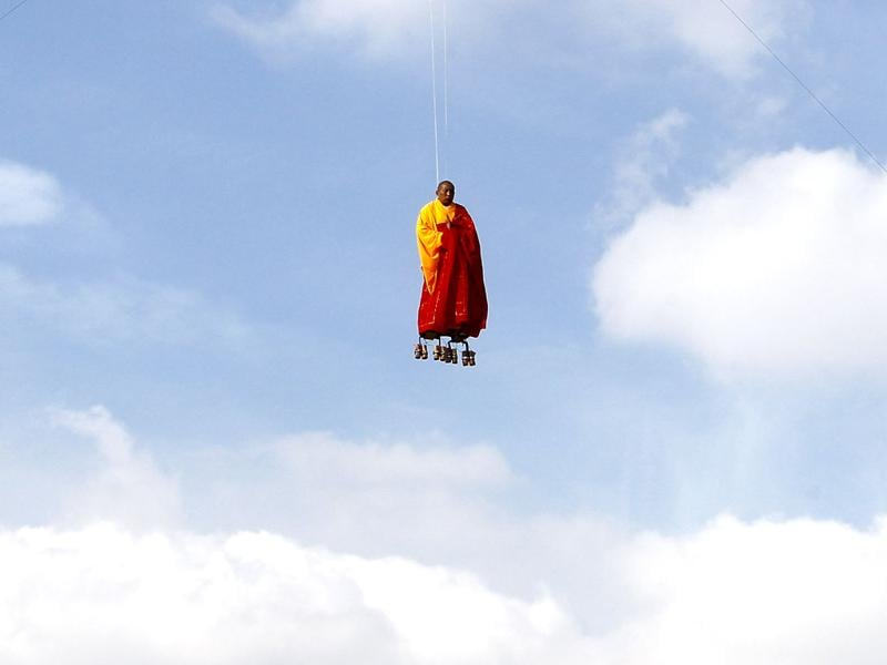 Suspended by wires, Chinese artist Li Wei performs in the sky at La Villette in Paris. Li Wei is a contemporary artist from Beijing, China. His work often depicts him in apparently gravity-defying situations. (AP Photo/Francois Mori)