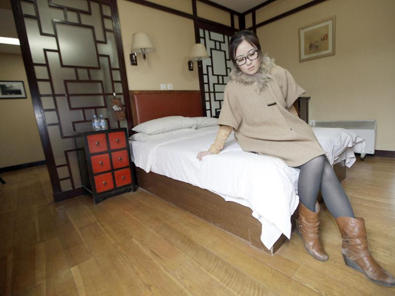 Zhuang, checks the bed of a Beijing traditional hotel with courtyard houses, known as