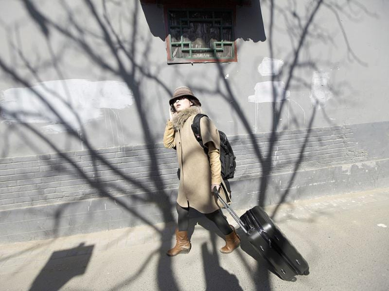 Zhuang, a Hotel Test Sleeper, uses her mobile phone as she looks for a boutique hotel along a traditional alleyway, or Hutong, in central Beijing. Zhuang was selected as one of three final winners out of 7,800 candidates and started working for Qunar as a Professional Hotel Test Sleeper. (Reuters)