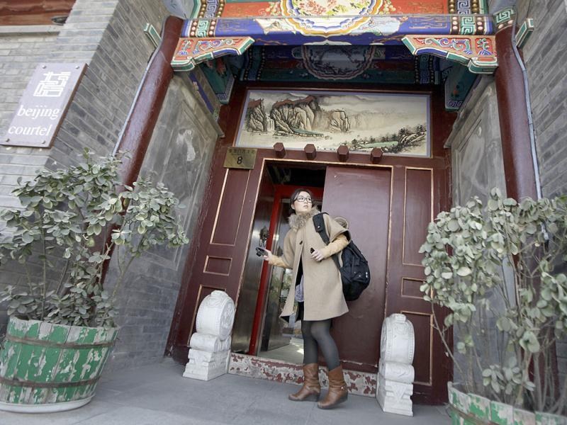 Zhuang, looks back at an entrance of a Beijing traditional hotel with courtyard houses, known as